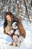 Muchacha que juega con su pequeño perro vestido Imagenes de archivo