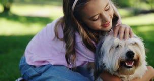 Muchacha que juega con su perro en el parque almacen de metraje de vídeo