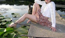Muchacha que juega con sus piernas? Foto de archivo