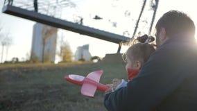 Muchacha que juega con un avión del juguete en el parque en un día soleado metrajes