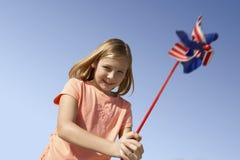 Muchacha que juega con un molinillo de viento Foto de archivo libre de regalías