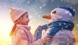 Muchacha que juega con un muñeco de nieve imagenes de archivo