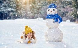 Muchacha que juega con un muñeco de nieve Imágenes de archivo libres de regalías