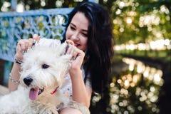 Muchacha que juega con un perro Fotos de archivo