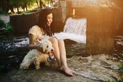 Muchacha que juega con un perro Fotografía de archivo libre de regalías