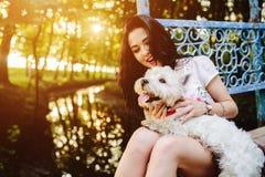 Muchacha que juega con un perro Foto de archivo
