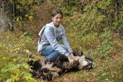 Muchacha que juega con un perro de montaña de Bernese Fotos de archivo