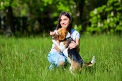 Muchacha que juega con un perro en el parque En las manos del palillo Foto de archivo libre de regalías