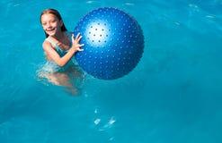 Muchacha que juega con una bola azul Fotografía de archivo libre de regalías