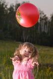 Muchacha que juega con una bola roja en el parque Fotos de archivo