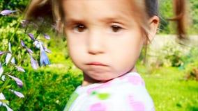Muchacha que juega con una flor y que mira la cámara ojos grandes de un niño metrajes