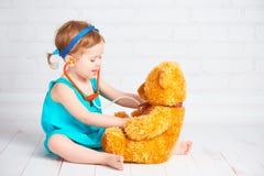 Muchacha que juega el doctor y el oso de peluche de las invitaciones Fotografía de archivo