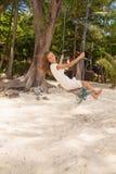 Muchacha que juega el oscilación en la playa Foto de archivo libre de regalías