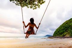 Muchacha que juega el oscilación en la playa Imagenes de archivo