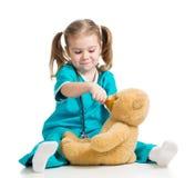 Muchacha que juega el oso de peluche del doctor que introduce y de la cuchara ov Fotos de archivo