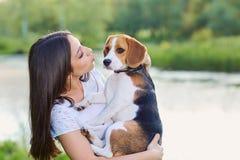 Muchacha que juega el perro casero del beagle del perrito que se besa al aire libre Fotos de archivo