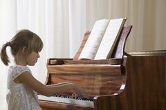 Muchacha que juega el piano Imagenes de archivo