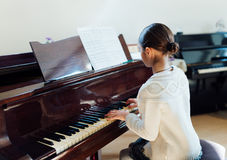 Muchacha que juega el piano de cola Foto de archivo