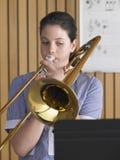 Muchacha que juega el trombón en clase de música Fotografía de archivo