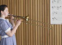Muchacha que juega el trombón en clase de música Imagen de archivo libre de regalías