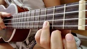 Muchacha que juega el ukelele Fotos de archivo