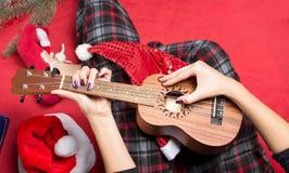 Muchacha que juega el ukelele para la Navidad foto de archivo
