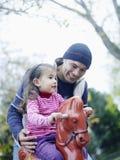 Muchacha que juega en caballo mecedora Imágenes de archivo libres de regalías