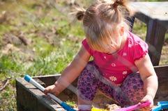 Muchacha que juega en caja de la arena Imagenes de archivo