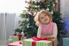 Muchacha que juega en el cuarto con un árbol de navidad Imágenes de archivo libres de regalías