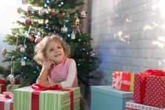 Muchacha que juega en el cuarto con un árbol de navidad Foto de archivo libre de regalías