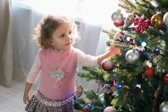 Muchacha que juega en el cuarto con un árbol de navidad Fotos de archivo libres de regalías