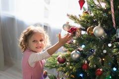 Muchacha que juega en el cuarto con un árbol de navidad Imagenes de archivo