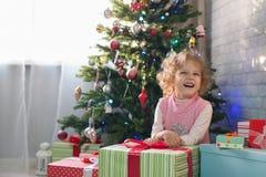 Muchacha que juega en el cuarto con un árbol de navidad Fotografía de archivo