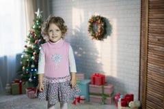 Muchacha que juega en el cuarto con un árbol de navidad Foto de archivo