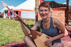 Muchacha que juega en el instrumento musical nacional del Kazakh - dombra y que se sienta cerca de Yurt Fotografía de archivo libre de regalías