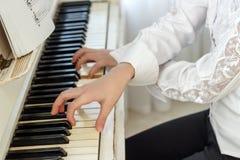 Muchacha que juega en el piano blanco Manos de una muchacha que pulsa teclas del piano imágenes de archivo libres de regalías