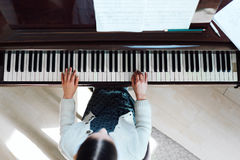 Muchacha que juega en el piano de cola, visión superior Fotos de archivo libres de regalías