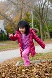 Muchacha que juega en hojas de la caída Foto de archivo