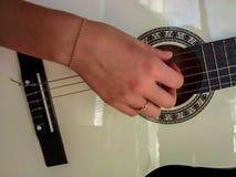Muchacha que juega en la guitarra clásica blanca Foto de archivo libre de regalías