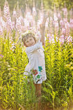 Muchacha que juega en un campo de flores Foto de archivo libre de regalías