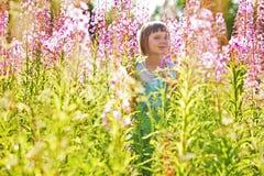 Muchacha que juega en un campo de flores imagenes de archivo