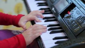 Muchacha que juega en un piano del juguete, primer almacen de video