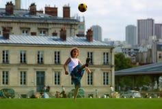 Muchacha que juega a fútbol en frente la construcción de escuelas Imágenes de archivo libres de regalías