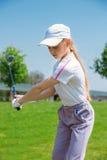 Muchacha que juega a golf Fotos de archivo