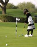 Muchacha que juega a golf Imagen de archivo