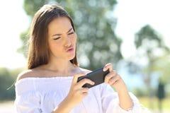 Muchacha que juega a juegos en el teléfono elegante Imagen de archivo libre de regalías