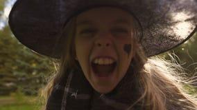 Muchacha que juega a la bruja malvada, rugiendo airadamente en la cámara, celebración del partido de Halloween metrajes