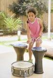 Muchacha que juega los tambores Foto de archivo libre de regalías