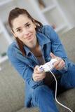 Muchacha que juega a los videojuegos que llevan a cabo el joypad Foto de archivo
