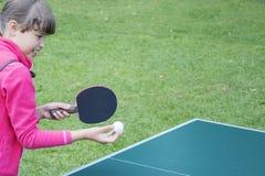 Muchacha que juega a ping-pong al aire libre en día soleado del verano Foto de archivo